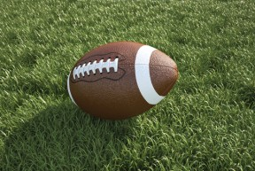 American football ball, on the grass. Close up.